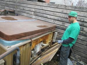 Derick checks for raccoon inside hot tub enclosure